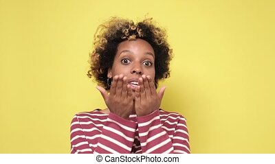 Pretty african woman makes an air kiss to the camera during a photo shoot in the studio. Positive facial human emotion.