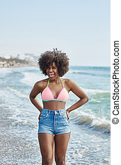 Pretty afro american girl standing in water laughing