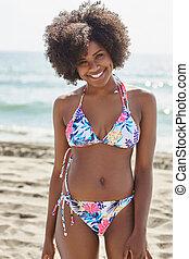 Pretty afro american woman in bikini standing on beach smiling