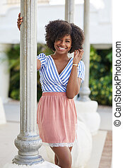Pretty afro american woman in dress behind column touching hair