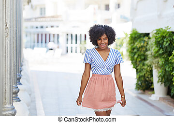 Pretty afro american woman in dress standing on the street