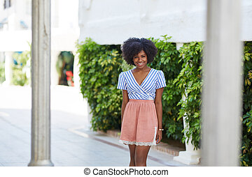 Pretty afro american woman in dress standing outside smiling