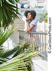 Pretty afro american woman leaning against fence outside