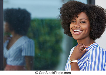 Pretty afro american woman standing against glass window