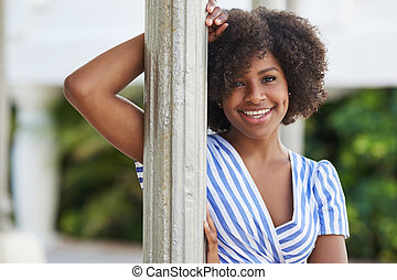 Pretty afro american woman standing behind column smiling
