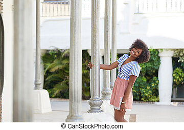 Pretty afro american woman standing next to column smiling