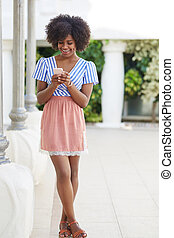 Pretty afro american woman using mobile smiling