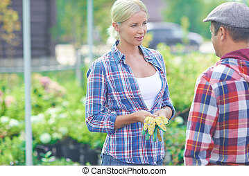 Pretty agriculturist - Two agricultural workers talking in...