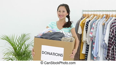 Pretty asian brunette holding donation box full of clothes...