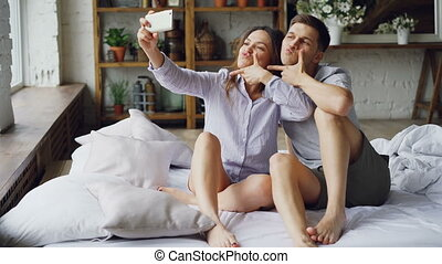 Pretty asian girl is taking selfie with her handsome caucasian boyfriend holding smartphone posing and kissing. Romantic relationship and social media concept.