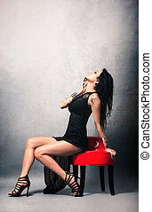 Pretty asian in black dress sitting on an armchair