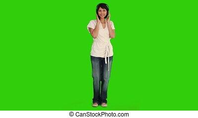 Pretty asian lady listening to music via a headphones -...