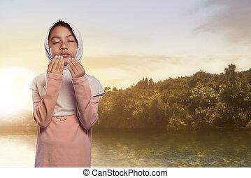 Pretty asian muslim child with hijab praying