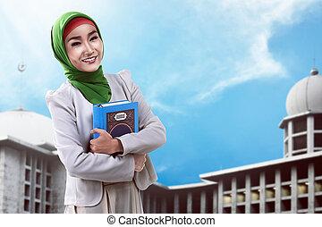 Pretty asian muslim woman holding koran