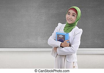 Pretty asian muslim woman holding the holy book Koran