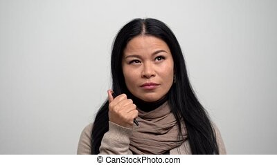 Pretty Asian thinks and clicks the button of a pen