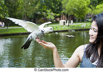 Pretty Asian woman and pigeon.