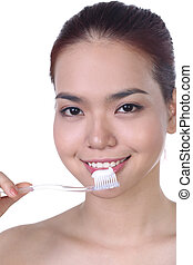 Pretty asian woman brushing teeth