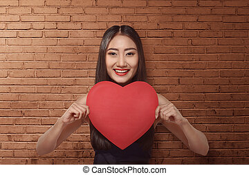 Pretty asian woman holding a paper heart