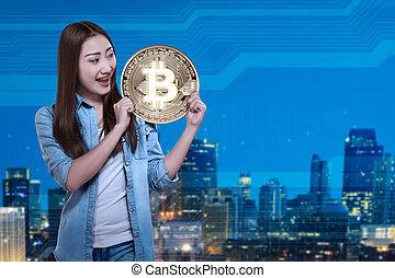 Pretty asian woman holding golden bitcoin