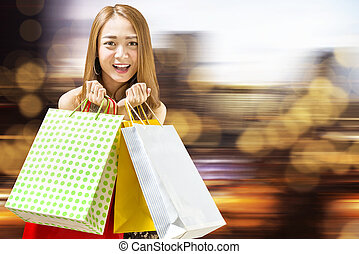 Pretty asian woman in black dress holding paper bags