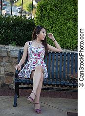 Pretty Asian woman on bench