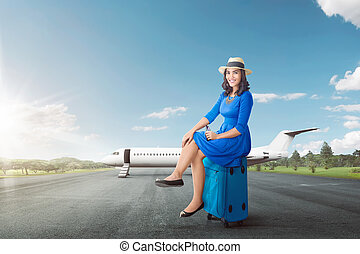Pretty asian woman sitting on suitcase