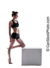 Pretty athletic brunette posing on cube