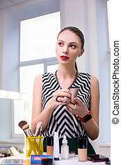 Pretty attractive woman choosing cosmetics for her