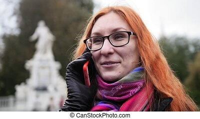 Pretty attractive young woman with red hair and glasses emotionally talking on phone in park - Burggarten, Vienna, close up