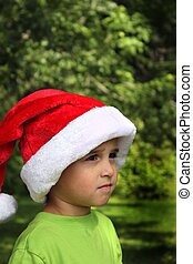 Pretty baby boy in green shirt and Santa hat