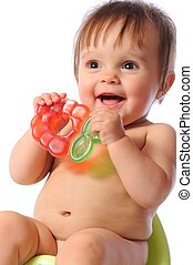Pretty baby child sits on potty and holds teether