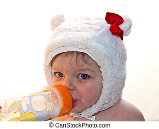 Pretty baby girl drinking milk from bottle