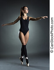Pretty ballerina dancing gracefully in studio