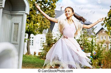 Pretty ballet dancer among the soap bubbles