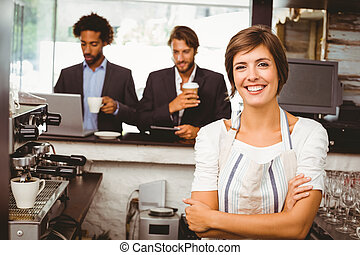 Pretty barista smiling at camera at the coffee shop