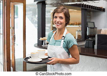 Pretty barista smiling at camera holding tray at the coffee...