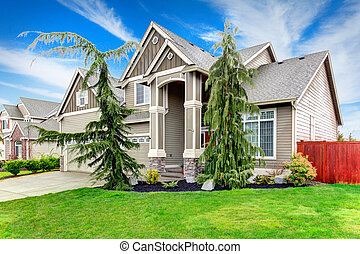 BIg siding house with porch columns stoned at base, tile roof and beautiful flower bed and trim