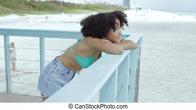 Pretty black girl enjoying view on beach - Young relaxed...