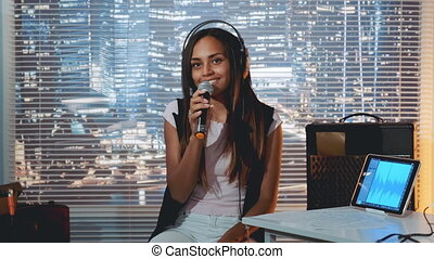 Pretty black girl in headphone singing into microphone and recording a song in home studio