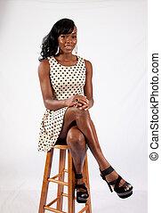 Pretty Black woman sitting on stool
