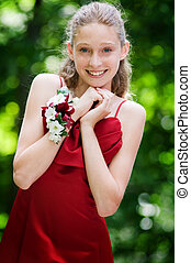 pretty blond blue eyed teen girl dressed in a gown to attend the school prom