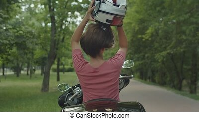 Pretty blond girl enjoying motorbike ride outdoor - Rear...