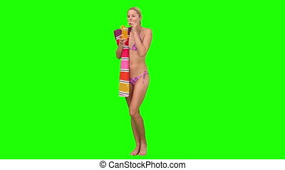 Pretty blond girl in swimsuit sipping a cocktail