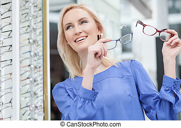 Pretty blond girl is choosing glasses in store