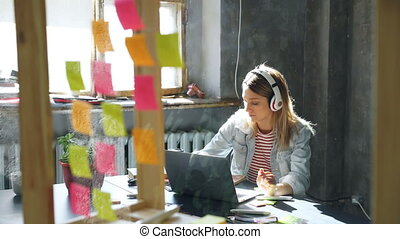 Pretty blond girl is listening to music and working with...