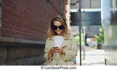 Pretty blond girl is using modern smartphone touching screen walking in city and smiling. Young woman is wearing fashionable clothing and trendy sun glasses.