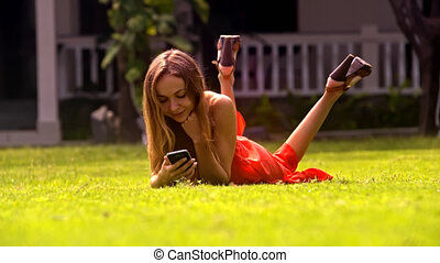 Pretty Blond Girl Lies on Grass with Phone in Park