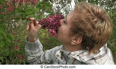 Pretty blond girl sniffing lilac flowers in park