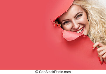 Pretty blond lady looking from behind of a red paper